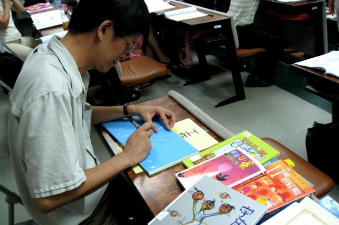 7/22上午場:兒童文學作家林世仁老師主講「童心看世界-童話書的魅力」。圖為林老師於演講後為本系實習圖書館藏書簽名。